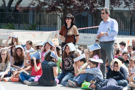 Photo pour THESSALONIKI, GREECE- APRIL 24, 2013: Children sitting at the school yard, protecting their heads with books. Earthquake exercise, drill. 6th primary school in Thessaloniki, Greece. - image libre de droit