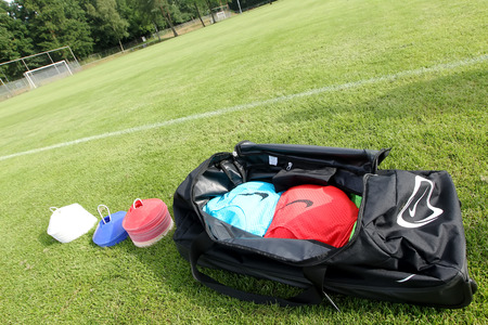 THESSALONIKI, GREECE – JULY 14, 2014: Soccer (football) training equipment next to a bag with the team's clothes during Paok training in Thessaloniki, Greece.