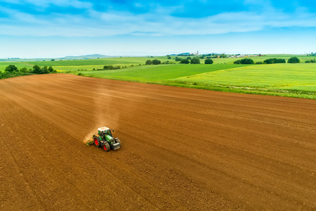 Photo pour Aerial shot of  Farmer with a tractor on the agricultural field sowing. tractors working on the agricultural field in spring. Cotton seed - image libre de droit