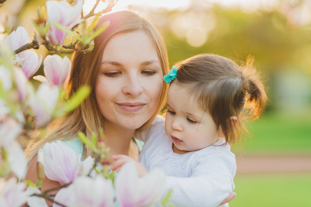 Photo pour young mother with adorable daughter at blossom tree - image libre de droit