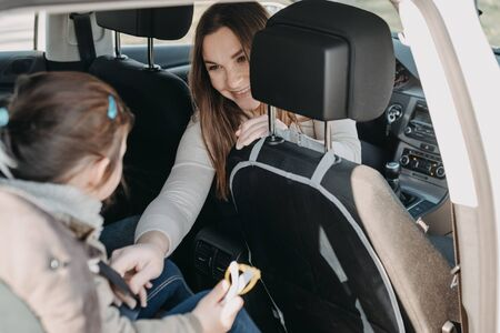 Photo pour Mother securing her toddler daughter buckled into her baby car seat from the front seat - image libre de droit