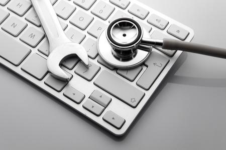 Foto de Electronic technical support concept - spanners on computer keyboard - Imagen libre de derechos