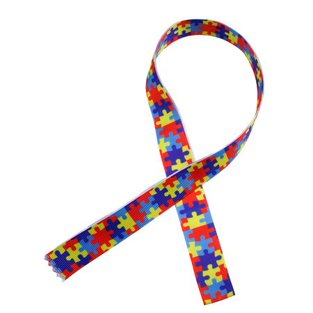 Foto de World Autism awareness and pride day with Puzzle pattern ribbon isolated on white - Imagen libre de derechos