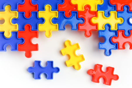 Foto de Pieces from a colorful jigsaw puzzle arranged to form a page on white background. Break barriers together for autism concept - Imagen libre de derechos