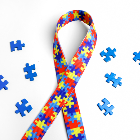 Foto de World Autism awareness and pride day with Puzzle pattern ribbon on white background with clipping path - Imagen libre de derechos