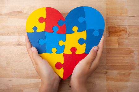 Foto de World Autism Awareness day, mental health care concept with puzzle or jigsaw pattern on heart with childs hands - Imagen libre de derechos