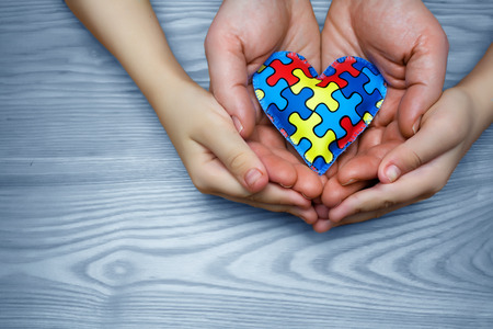Foto de World Autism Awareness day, puzzle or jigsaw pattern on heart with autistic childs and father hands - Imagen libre de derechos