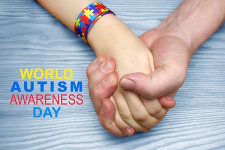 Foto de Autism Awareness Picture. Father holding hand his autistic child - Imagen libre de derechos