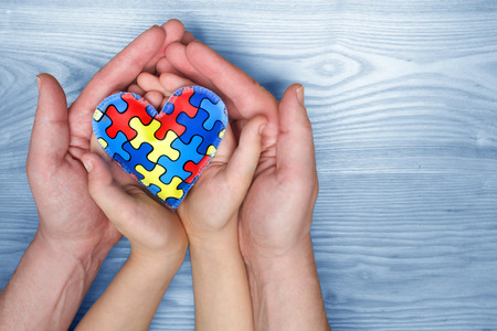Photo pour World Autism Awareness day, puzzle or jigsaw pattern on heart with autistic childs and father hands - image libre de droit