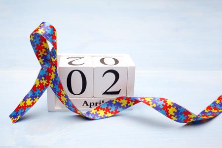 Foto de World Autism awareness and pride day with Puzzle pattern ribbon and calendar on blue wooden background - Imagen libre de derechos