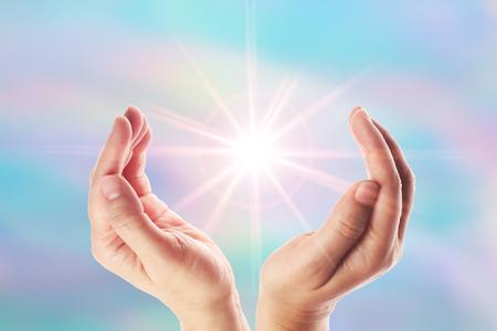 Foto de Healing hands with bright sunburst on rainbow background - Imagen libre de derechos