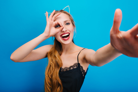Beautiful blonde with cat ears having fun at party, masquerade, carnival, smiling, taking selfie. Has wavy long hair. Wearing beautiful black dress with lace, bright makeup.