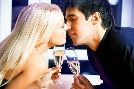 Young happy amorous couple with champagne kissing at party