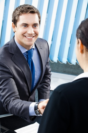 Two happy businesspeople or businessman and client handshaking at office