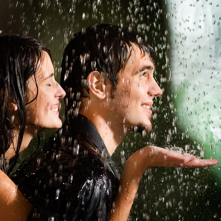 Young happy amorous couple under a rain, outdoors