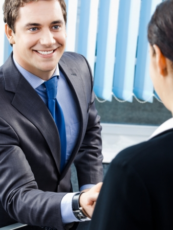 Two happy smiling cheerful businesspeople or business man and client handshaking at office