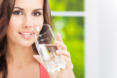 Portrait of young woman drinking water, outdoor, with copyspace