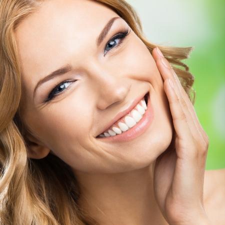 Foto de Portrait of happy smiling beautiful young woman touching skin or applying cream, outdoors - Imagen libre de derechos