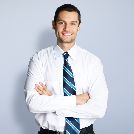 Photo for Portrait of happy smiling young businessman with crossed arms pose, against grey background - Royalty Free Image