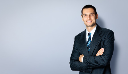Foto de Happy smiling businessman with crossed arms pose, with blank copyspace area for text or slogan, against grey background - Imagen libre de derechos