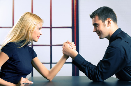 Photo for Young happy couple or two businesspeople fighting in arm wrestling, at office - Royalty Free Image