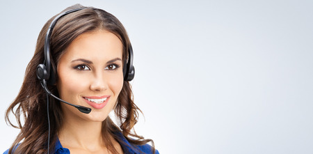 Foto de Portrait of happy smiling young support phone operator or businesswomen in headset, with blank copyspace area for slogan or text - Imagen libre de derechos