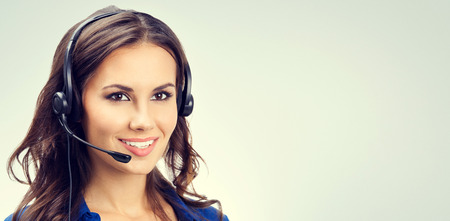Photo for Cheerful smiling young support phone operator or businesswomen in headset, with blank copyspace area for slogan or text. Customer service concept. - Royalty Free Image