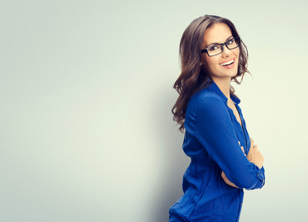 Foto de Cheerful smiling young businesswoman in glasses, with blank copyspace area for slogan or text - Imagen libre de derechos