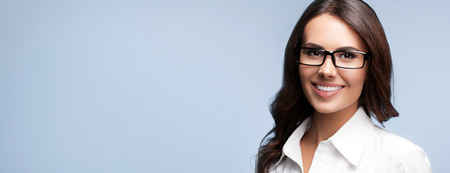 Photo pour Portrait of happy smiling brunette businesswoman in glasses, over grey background - image libre de droit