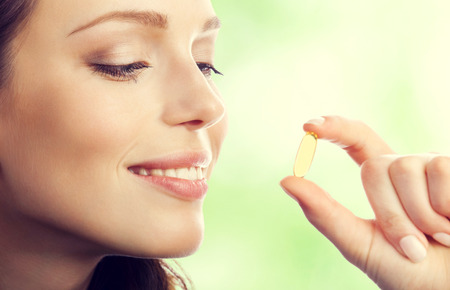 Photo pour Young smiling lovely brunette woman with Omega 3 fish oil capsule, outdoor - image libre de droit