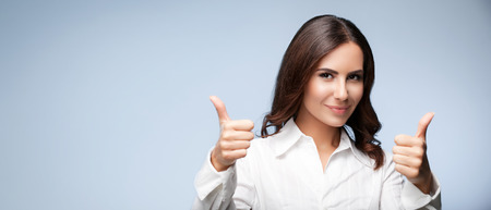 Portrait of happy smiling young cheerful businesswoman, showing thumb up hand sign gesture, with blank copyspace area for slogan or text message, over grey background