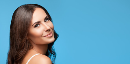 Portrait of happy smiling young beautiful woman in white casual clothing, over blue background, with copyspace area for slogan or text