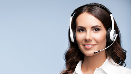 Photo pour Female customer support phone operator in headset, against grey background, with copyspace area for slogan or text message - image libre de droit