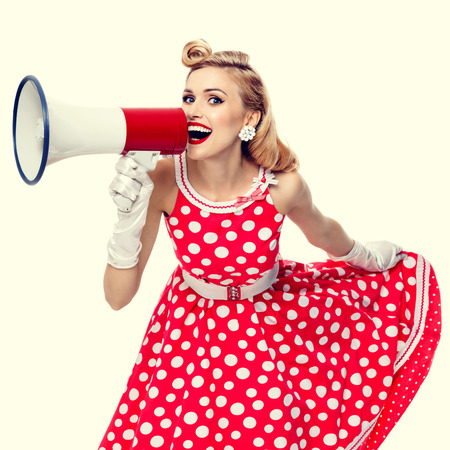 Photo for Portrait of beautiful young happy woman holding megaphone, dressed in pin-up style red dress in polka dot and white gloves. Caucasian blond model posing in retro fashion and vintage concept studio shoot. - Royalty Free Image