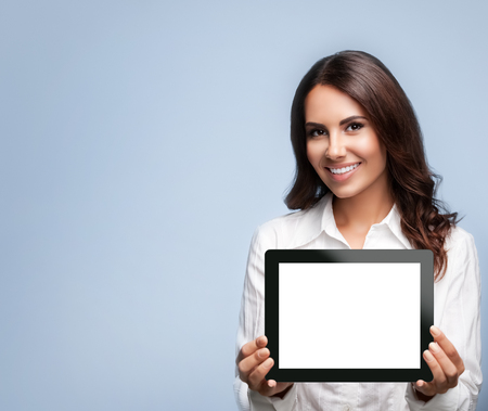 Foto de Smiling beautiful young brunette businesswoman showing blank no-name tablet pc monitor, over grey background, with copyspace area for slogan or text message - Imagen libre de derechos