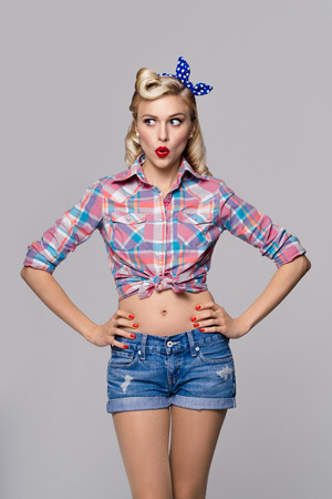 Photo pour Portrait of beautiful young surprised woman, dressed in pin-up style. Caucasian blond model posing in retro fashion and vintage concept studio shoot, on grey background. - image libre de droit
