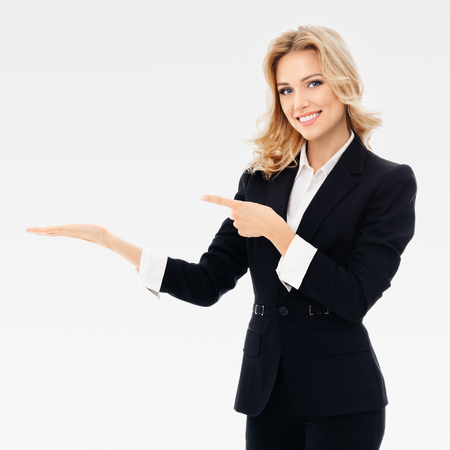 Foto de Portrait of smiling young cheerful businesswoman, showing something or blank copyspace area for slogan or text message, on grey background. Caucasian blond model in business presentation or sales advertision concept. Square composition. - Imagen libre de derechos