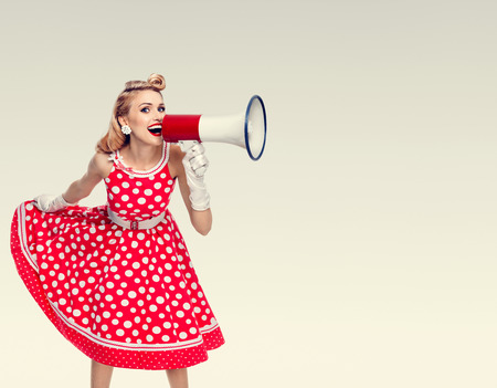 Photo for Portrait of woman holding megaphone, dressed in pin-up style red dress in polka dot and white gloves. Caucasian blond model posing in retro fashion vintage studio shoot. Copyspace area for advertising slogan or text message. - Royalty Free Image
