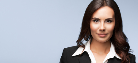 Portrait of happy smiling beautiful young businesswoman, on grey background. Brunette model in black suit - business success concept. Copyspace empty area for some text message or advertise slogan.