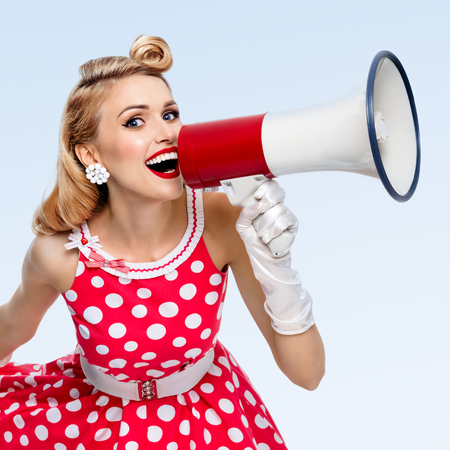 Photo pour Portrait of woman holding megaphone, dressed in pin-up style red dress in polka dot and white gloves, on blue background. Caucasian blond model posing in retro fashion vintage studio shoot. - image libre de droit