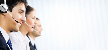 Foto de Three happy customer support phone operators at office, with copyspace area for text, advertisiment or slogan. Consulting and assistance service call center. - Imagen libre de derechos