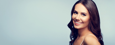 Portrait of beautiful cheerful smiling young woman, on grey background. Copyspace area for advertising slogan or text message.