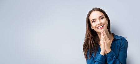 Photo for Portrait of happy gesturing smiling young woman in casual smart blue clothing, on grey background, with copyspace area for advertisiment, text or slogan. Advertising concept. Horizontal banner composition. - Royalty Free Image