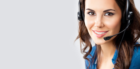 Portrait of happy smiling cheerful beautiful young female support phone operator in headset, over grey background, with blank copyspace area for advertising slogan or text message. Caucasian brunette model in help servise and client consulting concept sho