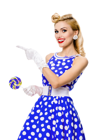 Photo for Happy smiling blond woman in pin-up style blue dress in polka dot, showing something or empty copyspace area for text, slogan or advertising message, isolated over white background. Caucasian model posing in retro fashion and vintage concept. - Royalty Free Image