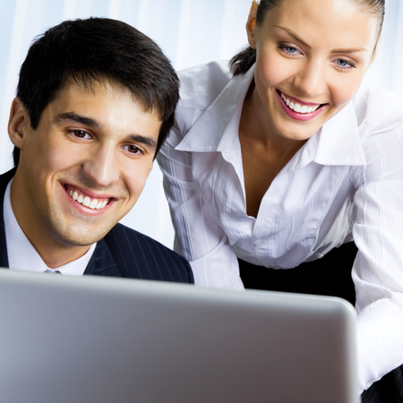 Photo for Two smiling young businesspeople working with laptop at office - Royalty Free Image