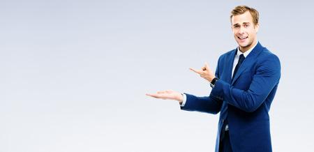 Foto de Bright image of businessman showing something, over grey background. Copyspace area for slogan or advertising text message. Success in business, job and education concept studio shot. - Imagen libre de derechos