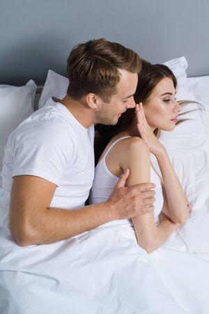 Foto de Unhappy young couple on the bed in bedroom. Caucasian models - in love crisis, relationship, frustrated concept shot. - Imagen libre de derechos