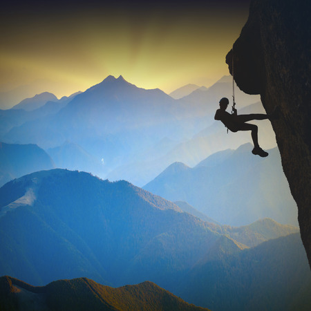 Silhouette of climber on a cliff against misty mountain valley