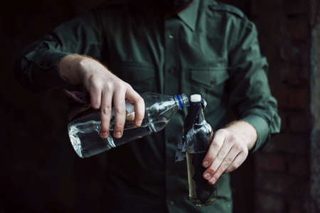 Dangerous bandit soak a wick of molotov cocktail with a fuel